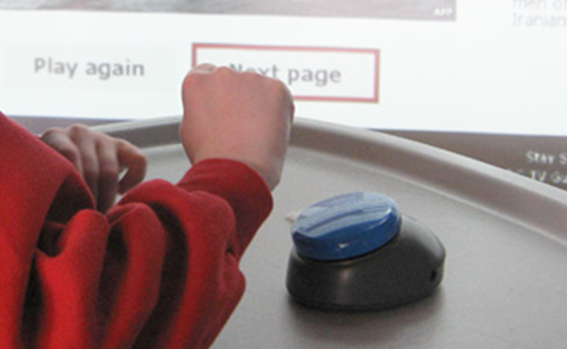 Child operating a computer by using a single large button mounted on a tray in front of her
