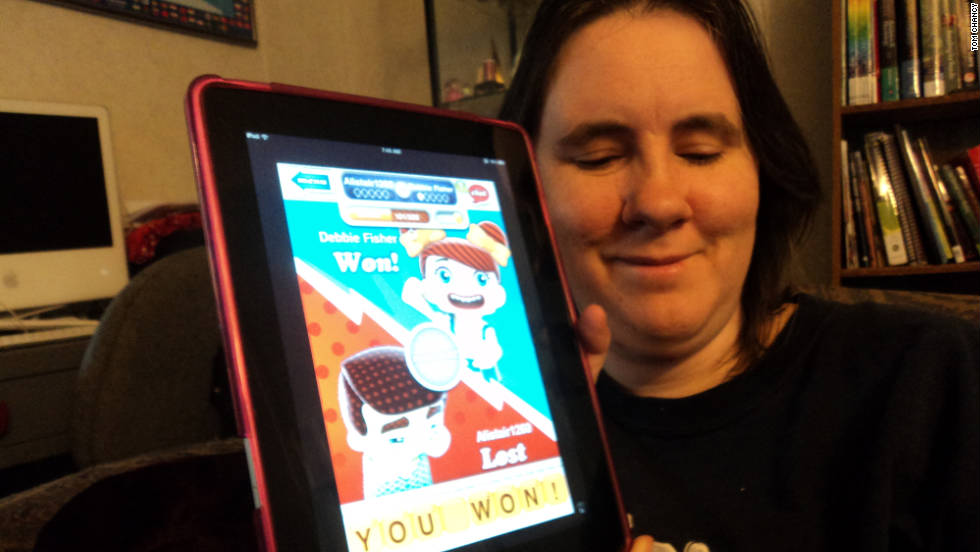 Debbie holding a tablet showing a hanging with friends endgame screen