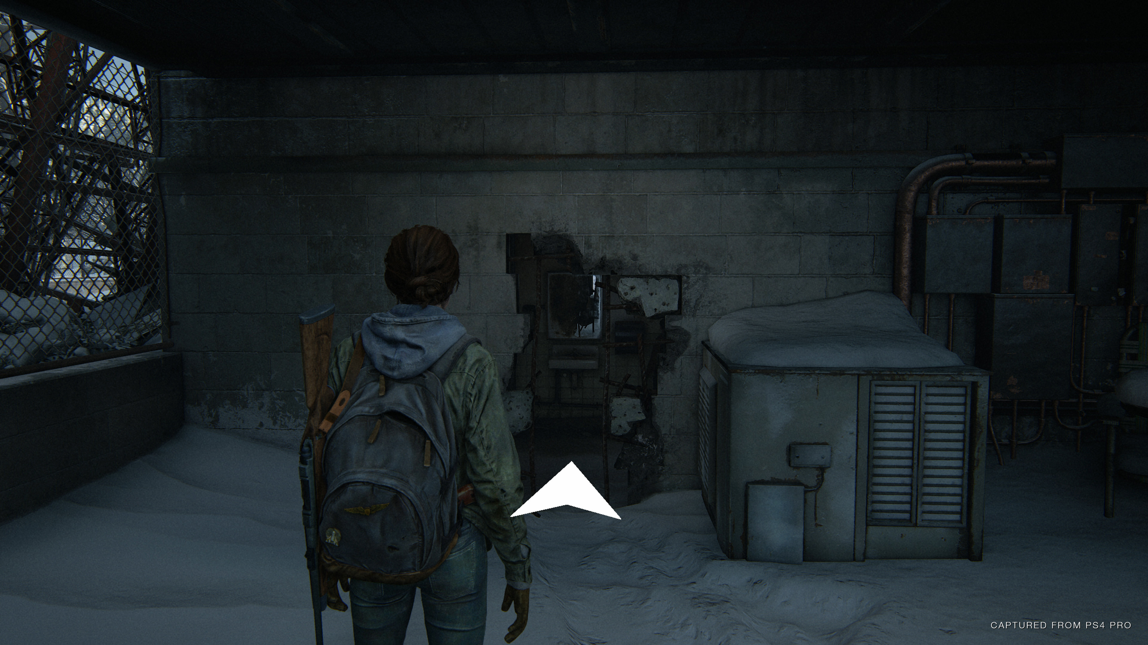 The player in front of a large hole in the wall, with a navigation assistance arrow pointing towards it